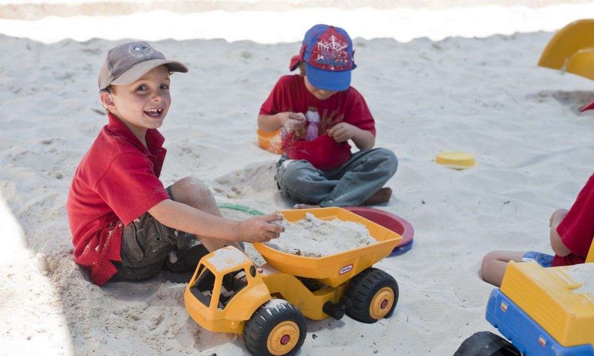Image of two boys playing with a truck in sandpit
